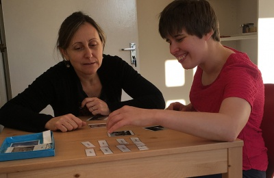 Nati supports one of the Cabrini House residents through a Montessori activity