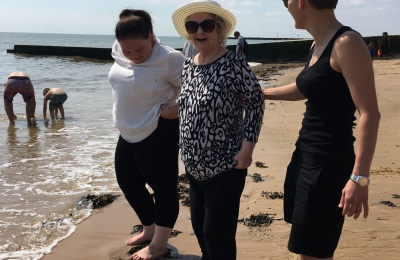 Edensor Care Centre staff help one of the residents take a paddle in the sea