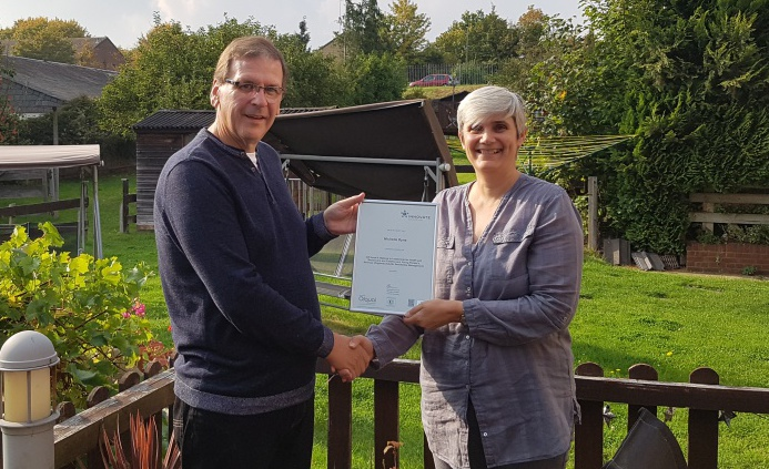 Diagrama Chief Operating Officer Derek Milliken presents Cabrini House residential manager Michelle Dyne with her certificate